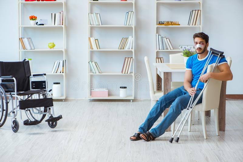 Young man recovering after surgery at home with crutches and a w. Heelchair stock photography