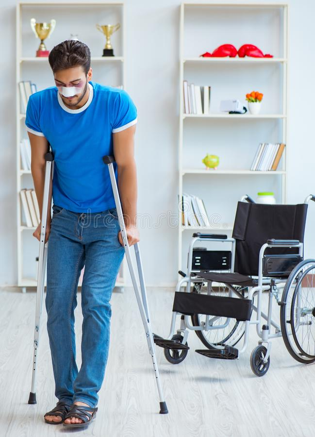 Young man recovering after surgery at home with crutches and a w. Heelchair royalty free stock images