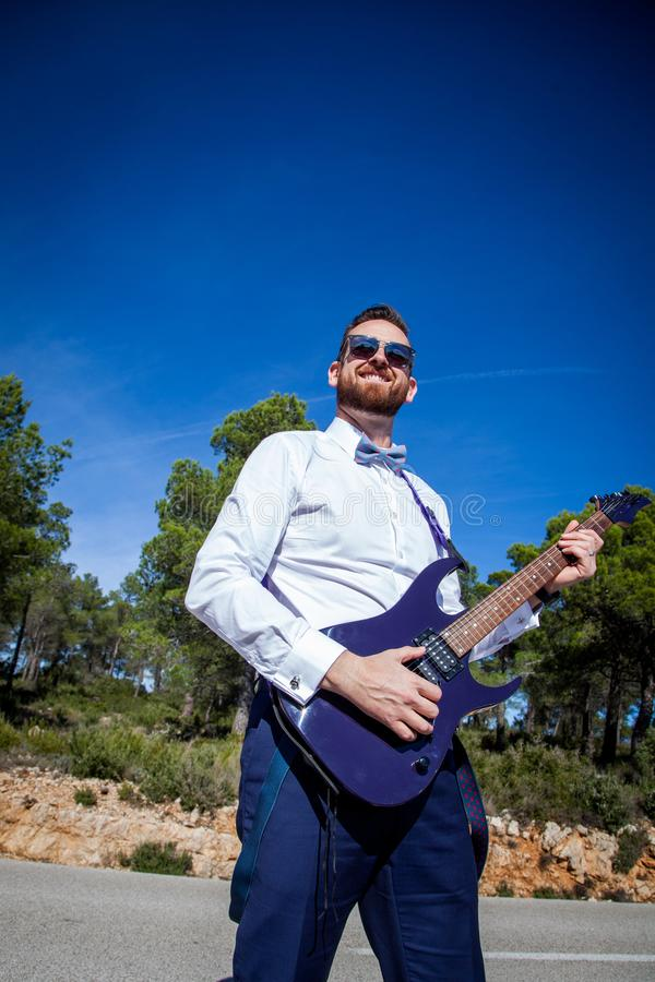 A young man with a red beard and an elegant dress holds an electric guitar in a forest. A young man with a red beard and an elegant dress holds an electric stock images