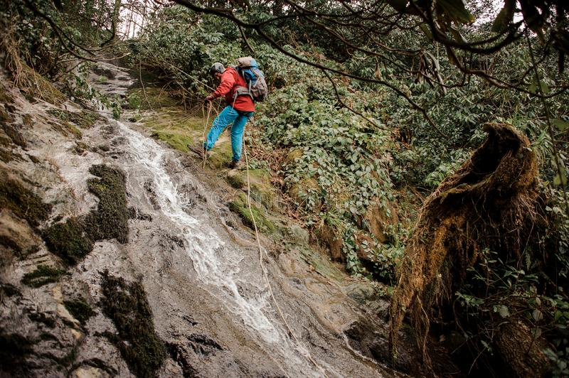 Young man dulfers down the mountains with waterfall in Adjara. Young man in red jacket with backpack dulfers down the mountains near waterfall in Adjara royalty free stock image
