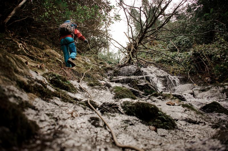 Young man dulfers down the mountains with waterfall in Adjara. Young man in red jacket with backpack dulfers down the mountains near waterfall in Adjara royalty free stock photo