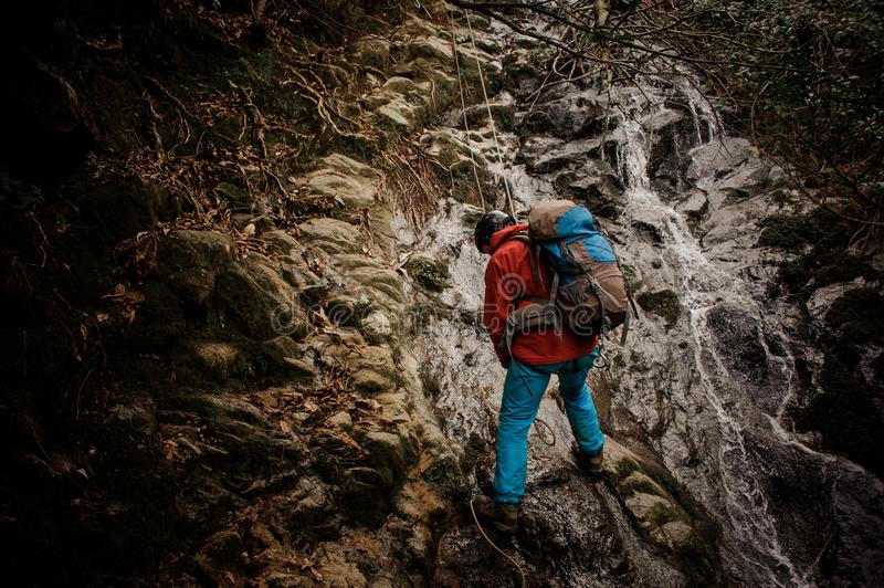 Young man dulfers down the mountains with waterfall in Adjara. Young man in red jacket with backpack dulfers down the mountains near waterfall in Adjara stock photos