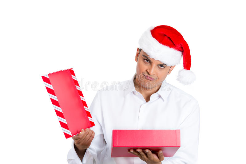Young man in red santa claus hat opening gift and very upset. Closeup portrait of young man in red santa claus hat opening gift and very upset at what he royalty free stock photo