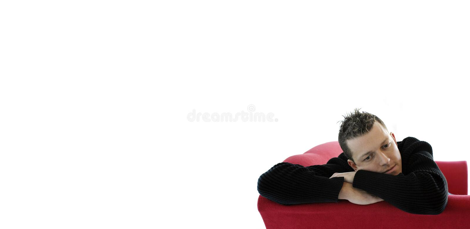 Young man on red sofa stock images