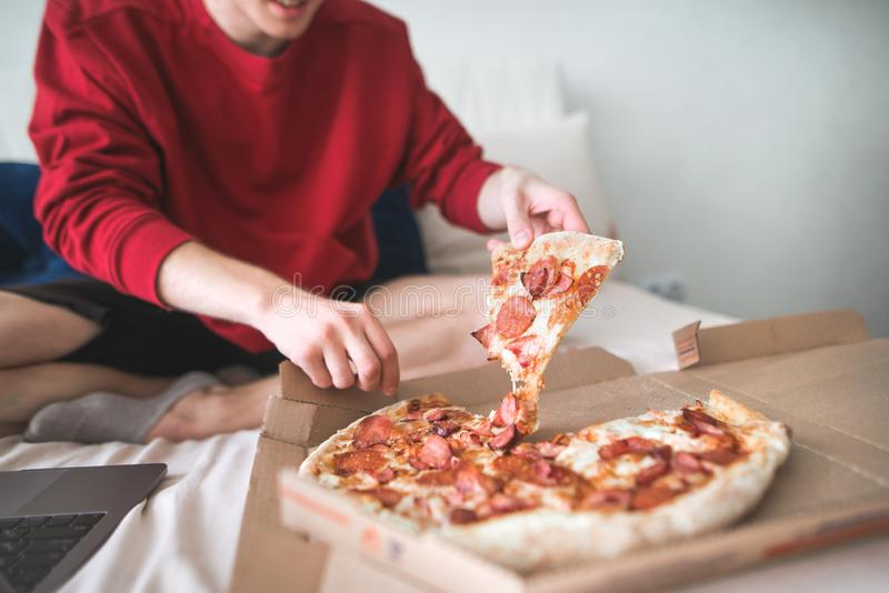 Young man in a red sweatshirt sits at home on a bed and takes an appetizing piece of pizza from the box royalty free stock photography