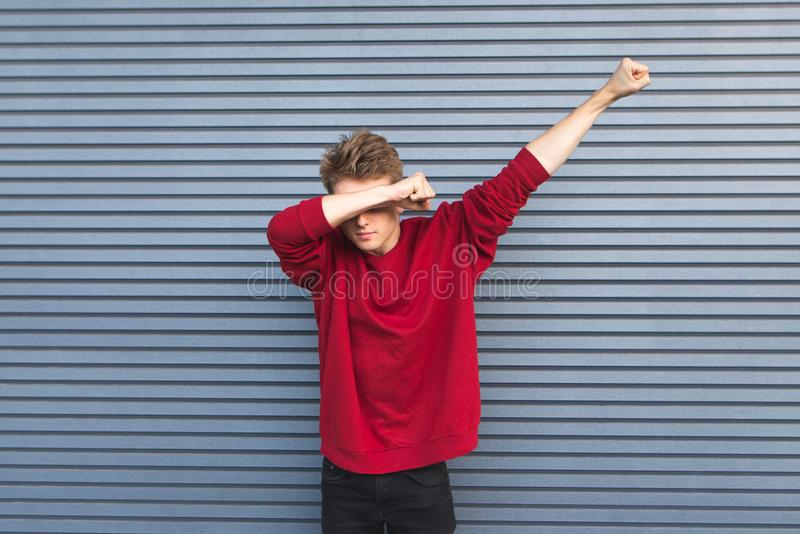 Young man in a red sweatshirt stands on the background of a gray wall and throws dab. Copyspace royalty free stock image