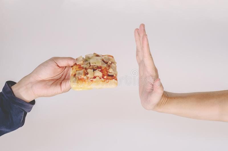 Young man rejecting pizza or unhealthy food. Dieting or good health concept. Unhealthy Eating Concept. A Young man rejecting pizza or unhealthy food. Dieting or stock images