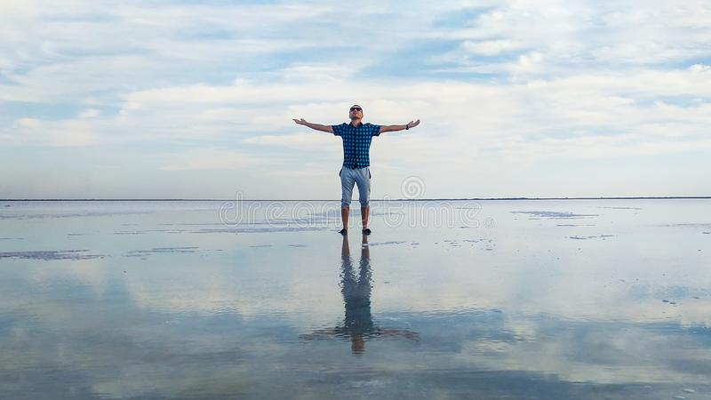 Young man is rejoicing by raising her hands up against the background of a blue sky with clouds and clear water in a salt lake. royalty free stock images