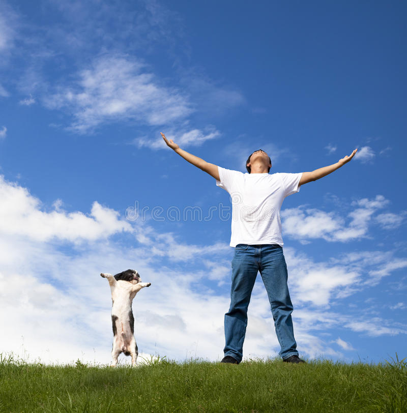 Young man relax and dog. Young man relax on the green field with his dog