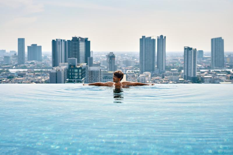 Young man relax on the edge of swimming pool in roof top of hotel. Summer vacation concept royalty free stock photography