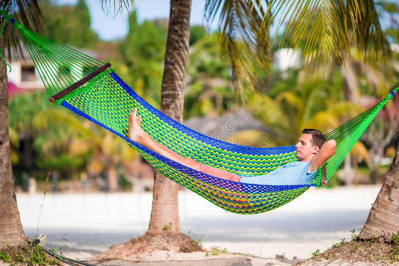 Young man relax in hammock. At tropical beach stock photography