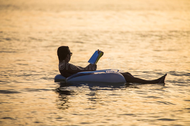 Young man in relax in the ocean water on inflatable ring on sunset read a book. Summer vocation royalty free stock photos