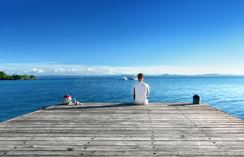 Young man relax siting. On pier stock photography