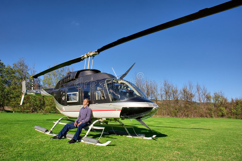 Young man relaxes next to small helicopter royalty free stock photo