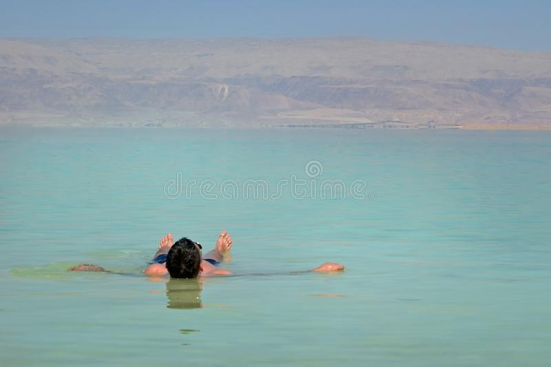The young man relaxes and swims in the water of the Dead Sea in Israel. tourism, health improvement, recreation, healthy lifestyle royalty free stock photo