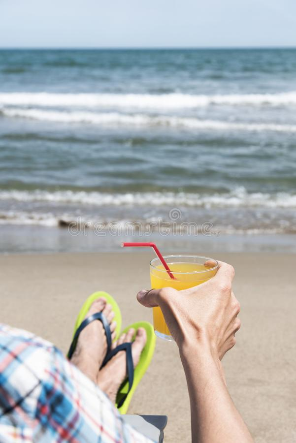 Young man relaxing on the beach. Closeup of a young caucasian man relaxing on the beach, sitting on a deck chair and wearing a pair of green flip-flops, with a royalty free stock photography