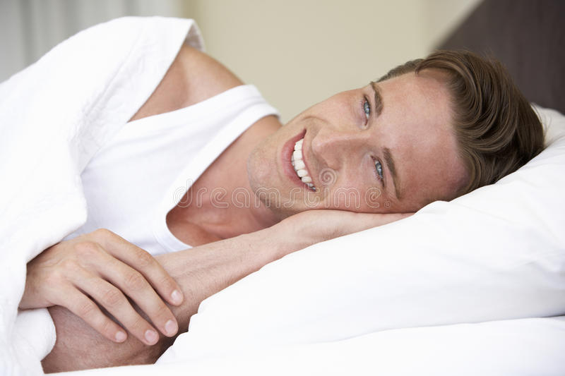 Young Man Relaxing On Bed stock photo