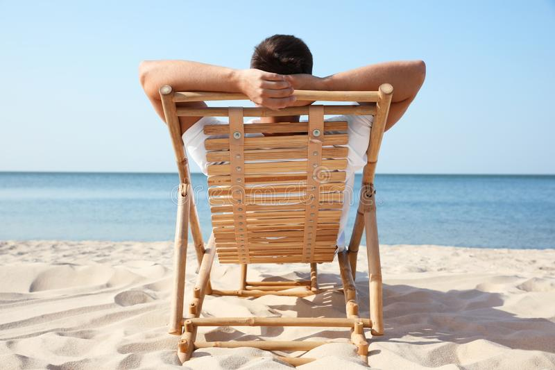 Young man relaxing in deck chair on  beach stock images