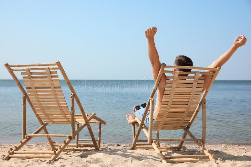 Young man relaxing in deck chair on = beach stock photos