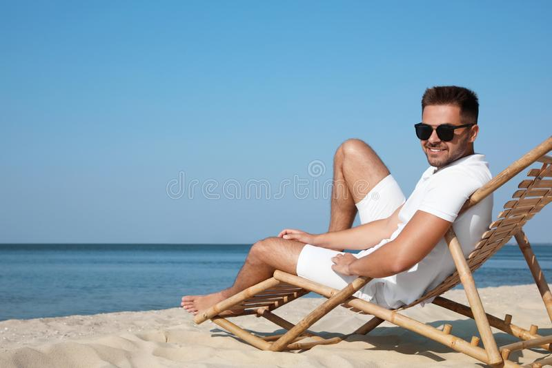 Young man relaxing in deck chair on sandy royalty free stock photo