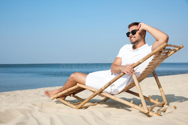 Young man relaxing in deck chair royalty free stock photos