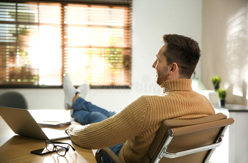 Young man relaxing at desk. In office stock photography