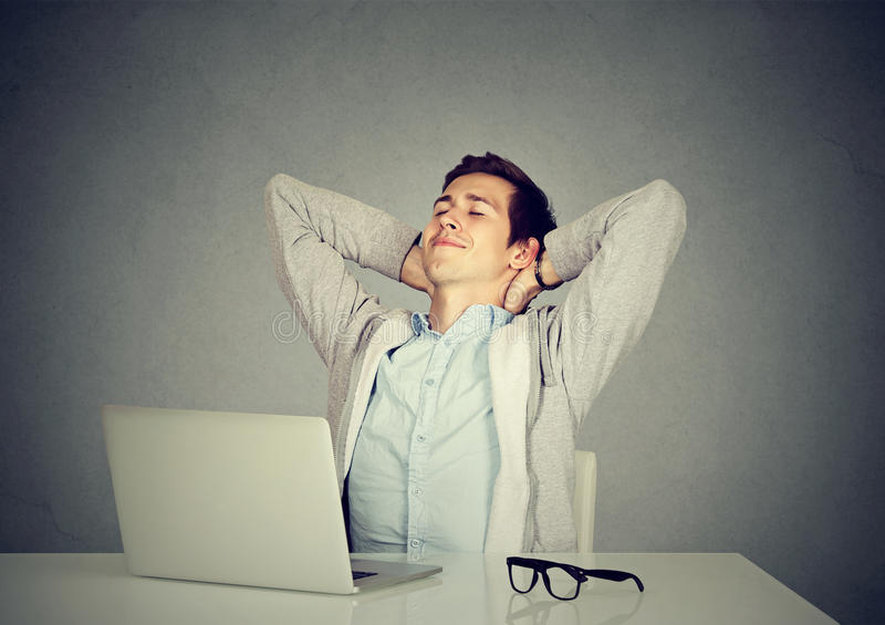 Young man relaxing at his desk royalty free stock photo