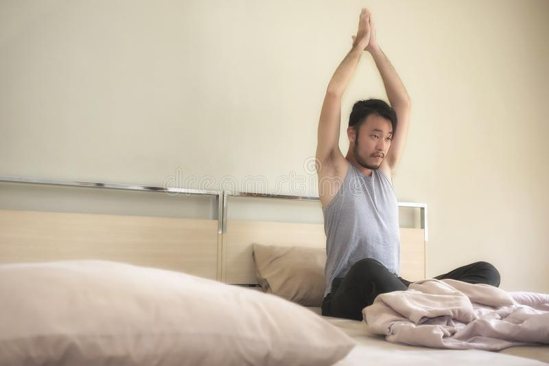 Young man relaxing yoga in bed after waking up in the morning. royalty free stock photos