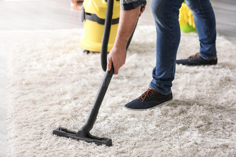 Young man removing dirt from carpet with vacuum cleaner royalty free stock images