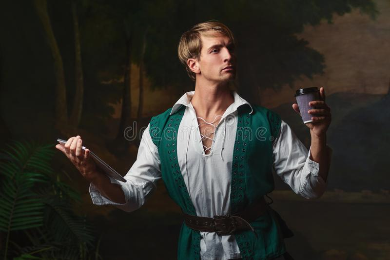 Young man in Renaissance style uses gadgets. Funny duet of medieval style and modern attributes, concept stock image
