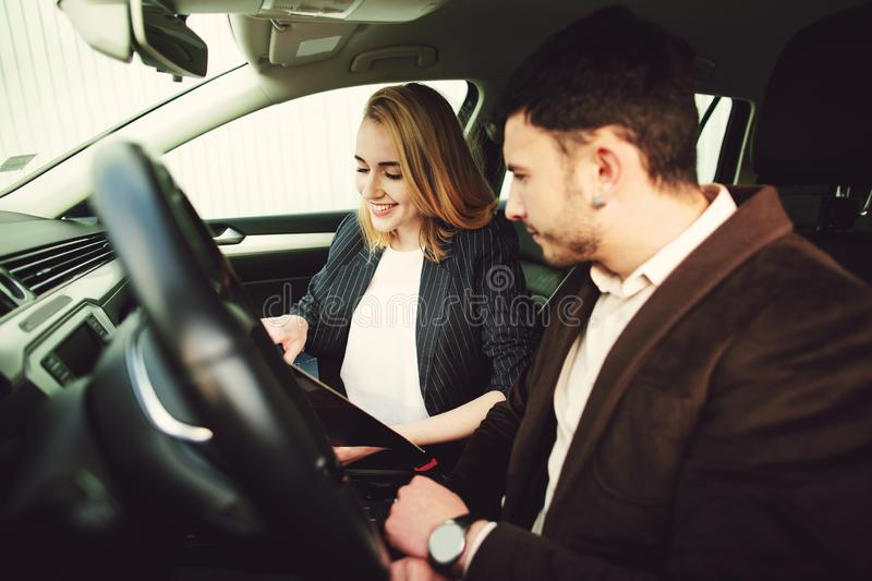 A young man rents a car. Employee of the dealer center shows documents in the car royalty free stock photo