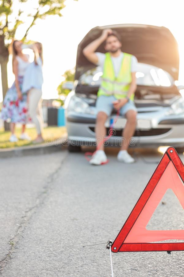 Young man repairing a broken car by the side of the road. Selective focus on emergency triangle in foreground stock image