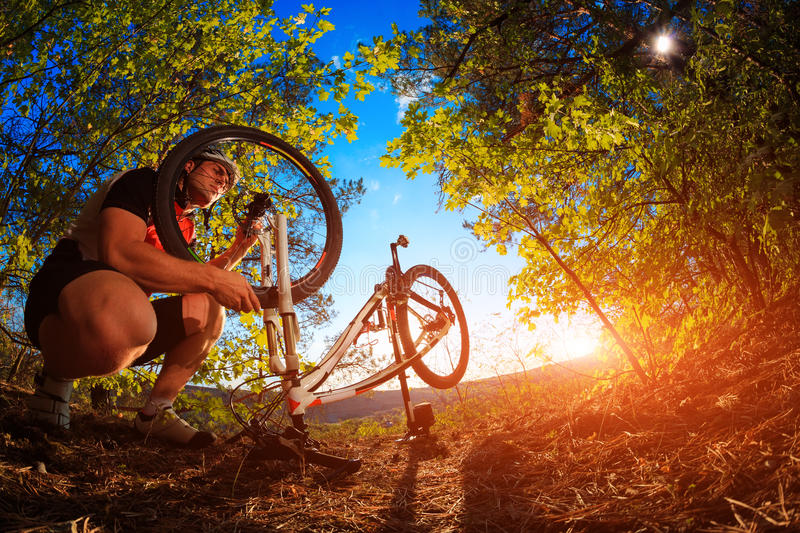 Young man repairing mountain bike in the forest. Bike repair. Young man repairing mountain bike in the forest royalty free stock photo