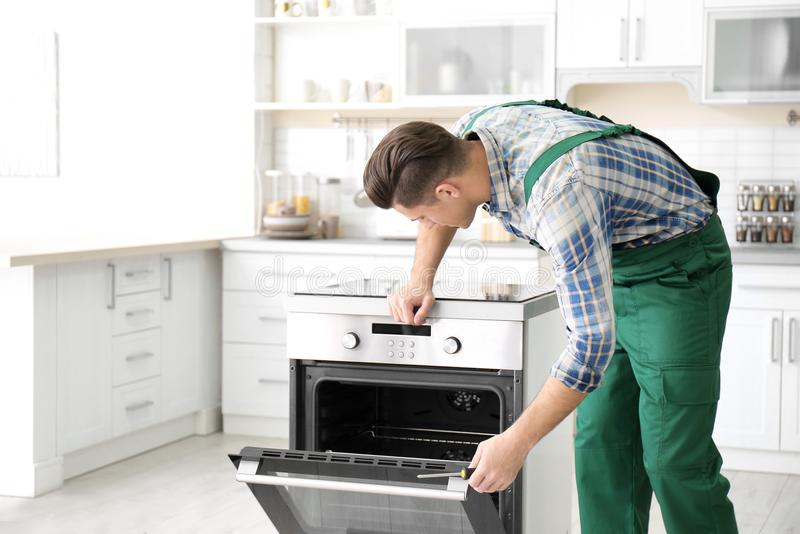 Young man repairing oven. In kitchen stock photo