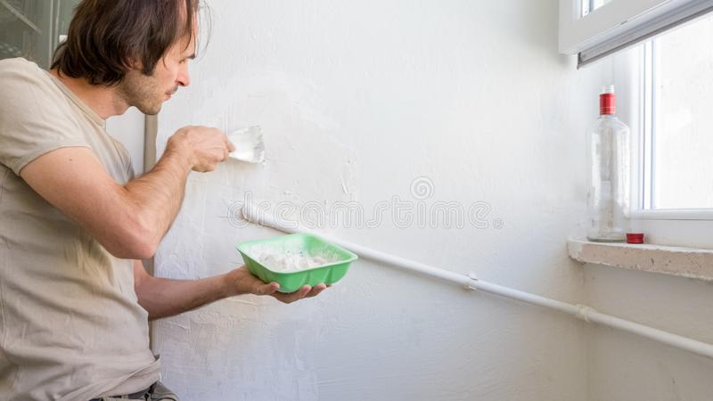 Young man repairing wall at his apartment, applying plaster mix on the wall royalty free stock images