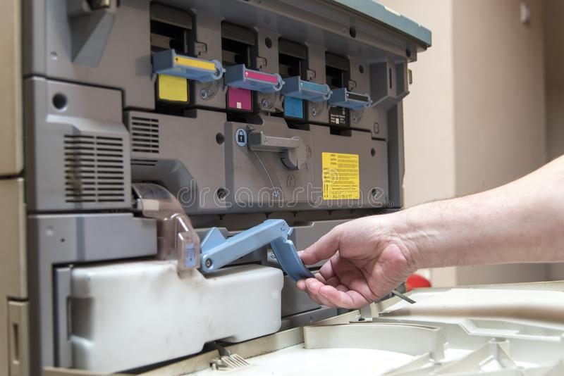 Young man replacing color toner inside a copier. Hand of a man replacing ink cartridge on a professional printing machine royalty free stock photos