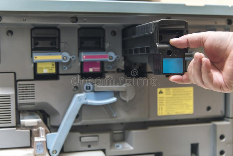 Young man replacing color toner inside a copier. Hand of a man replacing ink cartridge on a professional printing machine stock photos