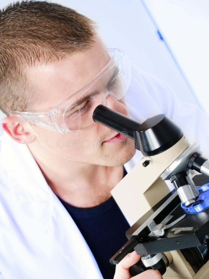 Young Man Researching On A Microscope Royalty Free Stock Photo