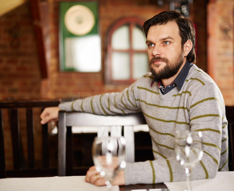 Young man in a restaurant. Young handsome man sitting in a restaurant and looking away stock image