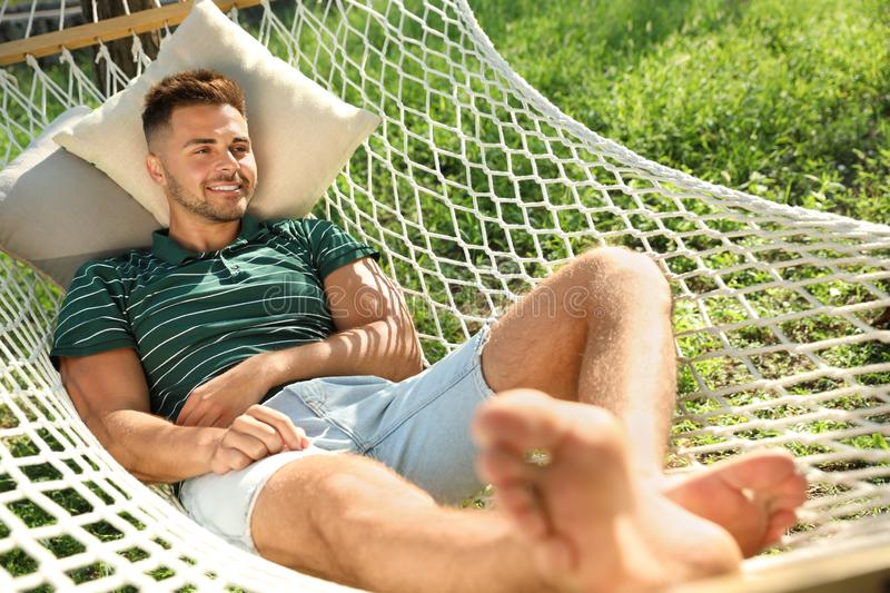 Young man resting in comfortable hammock at garden royalty free stock photos