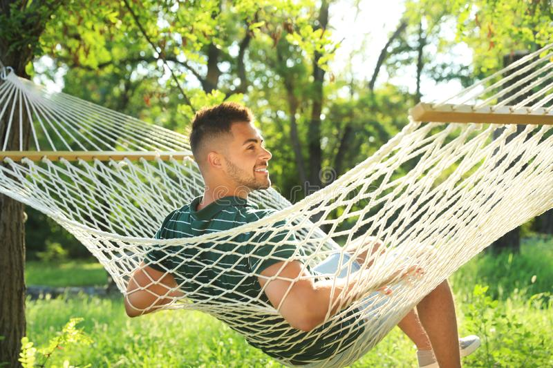 Young man resting in comfortable hammock at garden royalty free stock image