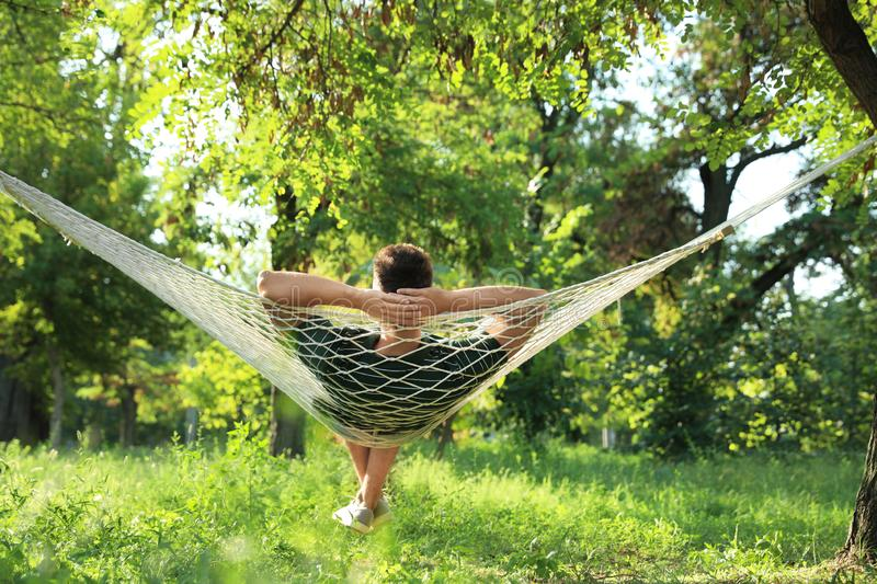 Young man resting in comfortable hammock at garden royalty free stock photography