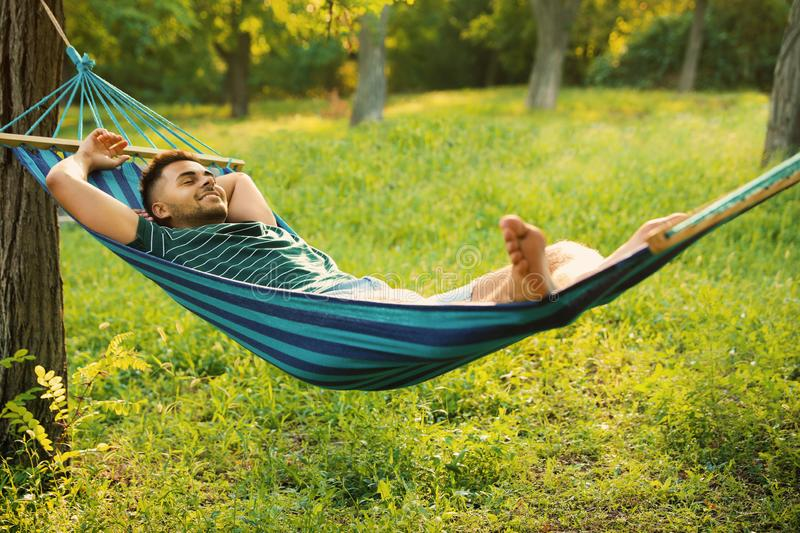 Young man resting in comfortable hammock royalty free stock photography