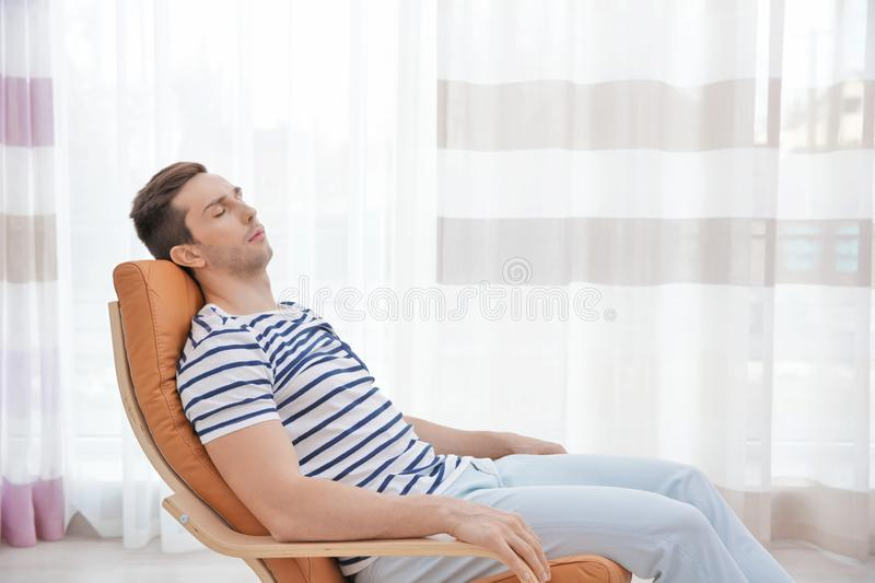 Young man resting on modern deck chair stock photo