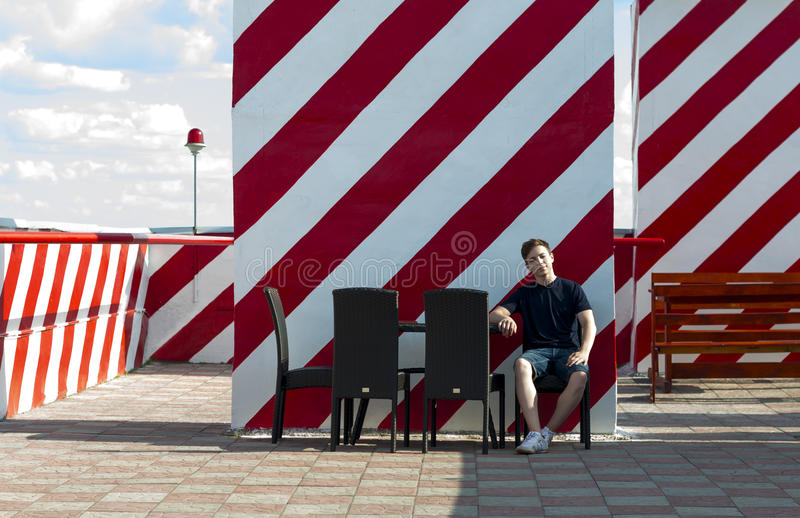 Young man is resting sitting at a table in a cafe royalty free stock photos