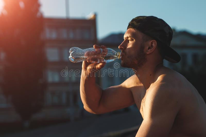 A young man is resting after a workout, drinking water, an athlete, training outdoors in the city copy space royalty free stock photography