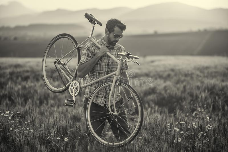 Young man with retro bicycle in sunset on the road, fashion photography on retro style with bike.  stock images