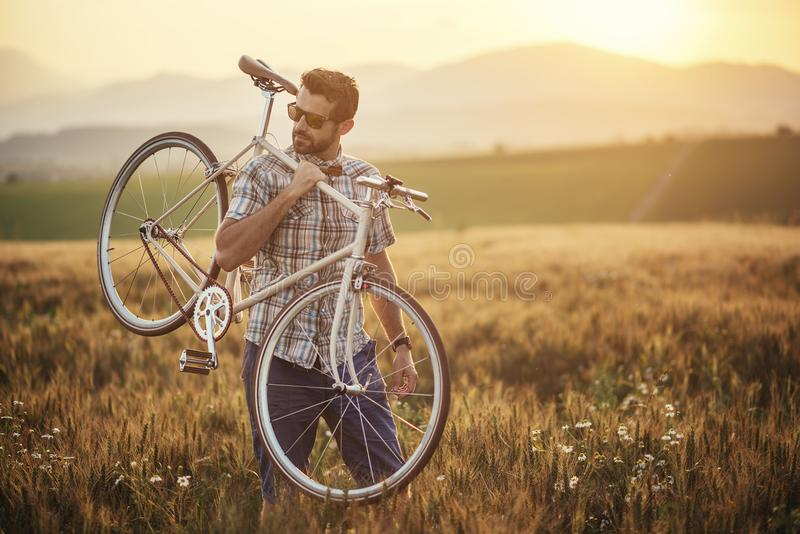 Young man with retro bicycle in sunset on the road, fashion photography on retro style with bike.  royalty free stock photo