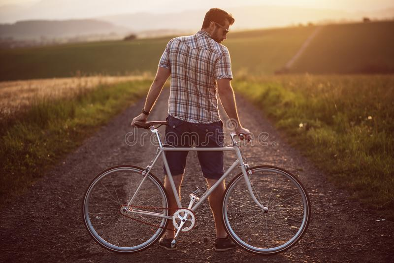 Young man with retro bicycle in sunset on the road, fashion photography on retro style with bike.  royalty free stock images