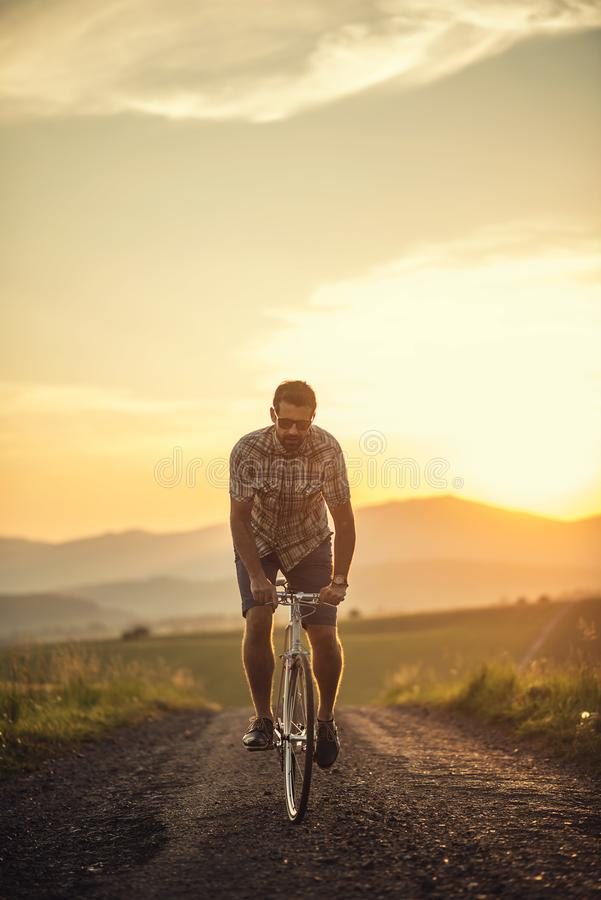 Young man with retro bicycle in sunset on the road, fashion photography on retro style with bike.  stock photos